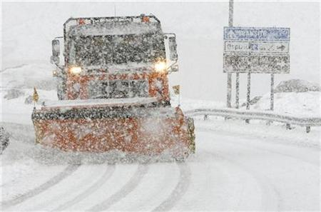 A worker drives a snow plough on the snow covered street of the Saint Gotthard mountain pass in the Swiss Alps September 14, 2008. REUTERS/Arnd Wiegmann