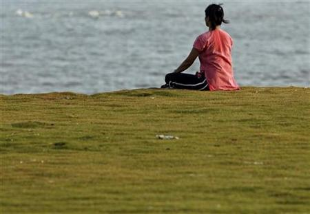 A woman practices yoga by the seaside in a file photo. REUTERS/Punit Paranjpe
