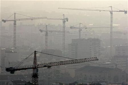 Construction cranes are seen over buildings in Marseille, October 14, 2008. REUTERS/Jean-Paul Pelissier