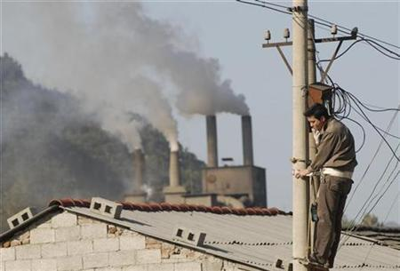 A man works on a power pole as smoke billows from chimneys in Baokang, Hubei province, October 23, 2008. REUTERS/Stringer