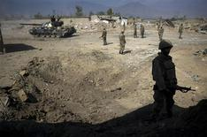 <p>Pakistan's army soldiers stand guard next to damaged houses in Loisam town, in the Bajaur tribal region, October 25, 2008. REUTERS/Emilio Morenatti/Pool</p>