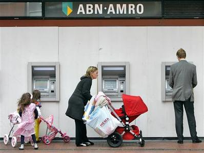 A woman pushes a pram outside ABN-AMRO Bank ATM machines in Amstelveen in this May 29, 2007 file photo. REUTERS/Koen van Weel/Files