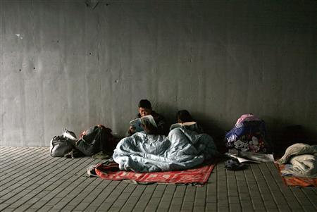 Migrant workers sit in their sleeping bags with their belongings as they wait for potential employers to arrive at an unofficial labour market located under a bridge in central Beijing October 30, 2008. The global economic slowdown, contrary to some predicitions, is taking its toll on China and threatens to swell its ranks of the unemployed, especially the rural migrant workers who have long streamed into cities to build office towers, clean streets and staff factories. Picture taken October 30, 2008. REUTERS/David Gray