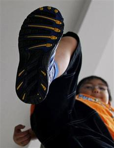 Six-year-old boy Kei Yamashita poses in ''Syunsoku'' shoes at a photo opportunity in Tokyo October 23, 2008. TREUTERS/Kim Kyung-Hoon