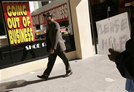 A man holds a sign asking for assistance outside a Shoe Pavilion store that is going out of business in the Financial District in San Francisco, California November 6, 2008. REUTERS/Robert Galbraith