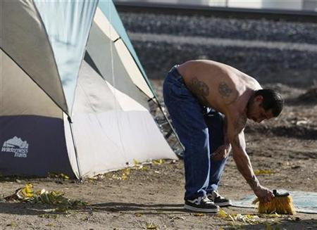 A man sweeps the area outside his tent with a broken broom at ''tent city'', a terminus for the homeless in Ontario, a suburb outside Los Angeles, California December 19, 2007. REUTERS/Lucy Nicholson