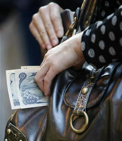 A woman holds money at a shop in Tokyo in this October 16, 2008 file photo. REUTERS/Kim Kyung-Hoon/Files