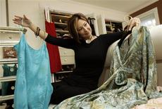 <p>Kathy Johnson looks through an assortment of dresses at her home in San Anselmo, California November 7, 2008. Last year at this time, Kathy Johnson and her husband traveled to London and Paris, where she spent about $2,000 on a shiny, red Louis Vuitton shoulder bag and a matching charm without much thought. This year Johnson, who runs a tech advisory firm with her husband in the San Francisco Bay area, is recycling older dresses to save money. Picture taken November 7. REUTERS/Robert Galbraith</p>