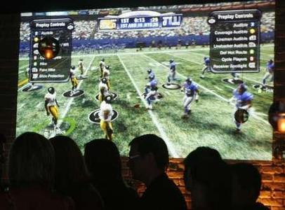 The videogame 'Madden NFL '09'' is projected on a wall at the Madden NFL '09 VIP Premiere party hosted by EA Sports and XBox in Los Angeles, California August 7, 2008. REUTERS/Fred Prouser