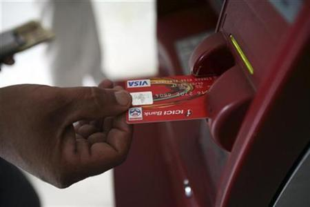 A customer uses his card to withdraw money from an ATM in Jammu October 14, 2008. REUTERS/Amit Gupta
