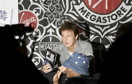 Singer Paul McCartney poses for photographers with a fan as he signs autographs for fans in celebration of the release of a new concert DVD and classical CD in New York City November 13, 2006. REUTERS/Lucas Jackson