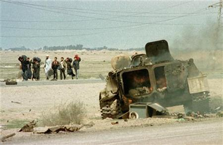 Kuwaiti citizens walk south along the Basra highway heading back to Kuwait following the end of the Gulf War, past a burning Iraqi APC destroyed by U.S. aircraft while retreating from Kuwait, February 28, 1991. REUTERS/Andy Clark