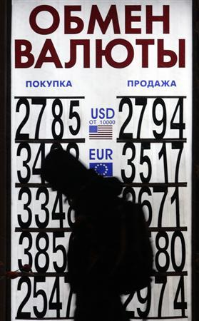 A walks past a currency exchange office in Moscow late November 20, 2008. Prime Minister Vladimir Putin assured Russians on Thursday he would guide them through the global financial crisis without the economic convulsions of the past, but acknowledged there would be pain. Picture taken November 20, 2008. REUTERS/Alexander Natruskin