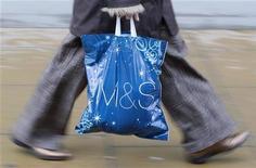 <p>Un acquirente con un sacchetto all'uscita da Marks and Spencer a Londra. REUTERS/Toby Melville (BRITAIN)</p>