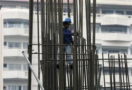 A worker fixes a steel bar in a condominium under construction along a street in Manila October 31, 2008. REUTERS/John Javellana