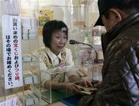 <p>A man buys a lottery ticket in the Ginza district of Tokyo November 25, 2008. REUTERS/Michael Caronna</p>