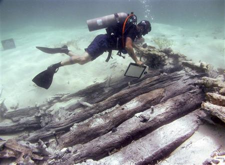 A marine archaeologist measures and compares the hull remains of the so-called 'Black Rock Wreck' to the dimensions of known shipwrecks off East Caicos in this undated handout photo provided by NOAA on November 25, 2008. A pair of glass-eyed idols led marine archaeologists to the wreck of a Spanish ship whose illegal cargo of African slaves are believed to be the ancestors of many of today's inhabitants of the British colony of Turks and Caicos. The U.S.-funded archaeologists said on November 24, 2008, they are confident the oaken timbers submerged under 9 feet (3 metres) of water off East Caicos island are the remains of the Spanish slave ship Trouvadore that sank in the Atlantic archipelago south of the Bahamas in 1841. REUTERS/National Oceanic and Atmospheric Administration/Handout