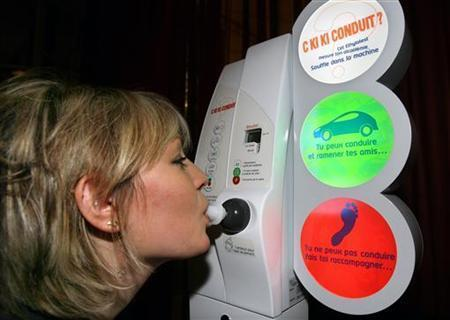 A woman demonstrates the use of an electronic breathalyzer test for discotheques, bars and public spots in Paris December 20, 2005. REUTERS/Charles Platiau