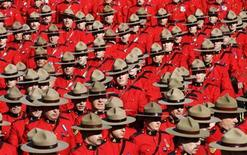 <p>Royal Canadian Mounted Police officers march during a memorial for four slain officers in Edmonton, Alberta, March 10, 2005. REUTERS/Shaun Best</p>