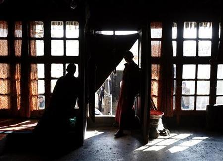 Buddhist monks stand in the entrance to a temple at the 1000-year-old Tsam Monastery located on a mountain at an elevation of over 4500 metres near the Tibetan city of Shigatse April 26, 2008. REUTERS/David Gray