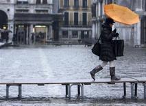 """<p>Mulher usando uma pasagem improvisada para passar pela praça de São Marcos, que está inundada emm um período de fortes chuvas em Veneza. Hotéis da região oferecem """"pacote inundações"""" com bota de brinde.REUTERS/Manuel Silvestri</p>"""