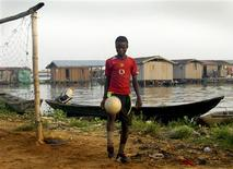 <p>A boy kicks a ball in Iwaya, one of the poorest areas of Lagos, in this undated photograph taken by a child, part of an exhibition in which hundreds of Nigerian kids from the richest and poorest homes in Lagos have documented their lives through pictures. REUTERS/Maxim Zannu/Handout</p>