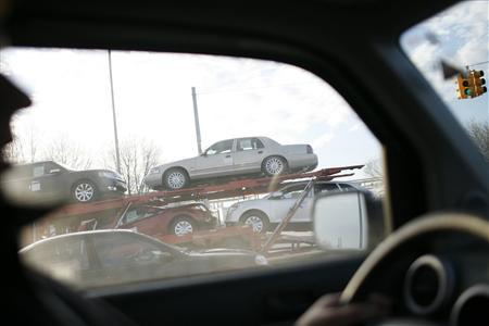 A truck filled with new cars leaves a parking lot next to a Chrysler plant in Detroit, Michigan December 10, 2008. REUTERS/Carlos Barria