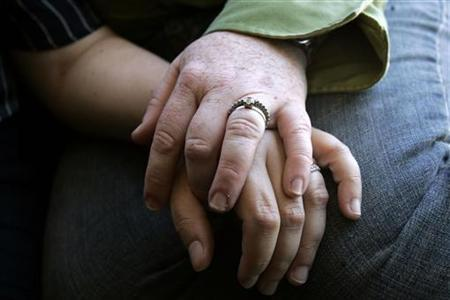 A lesbian couple hold hands as they look at a wedding photo at their home in San Francisco, California June 11, 2008. REUTERS/Erin Siegal