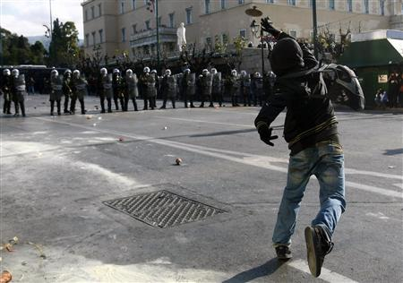 A protester throws a stone at policemen guarding Greece's parliament in Athens December 10, 2008. REUTERS/Yiorgos Karahalis