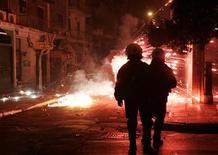 <p>Греческие полицейские наблюдают за тем, как горят бутылки с зажигательной смесью, использованные демонстрантами во время беспорядков в Афинах 14 декабря 2008 года. Беспорядки и акции протеста продолжаются в Греции в понедельник спустя восемь дней после убийства полицейскими 15-летнего подростка. REUTERS/John Kolesidis</p>