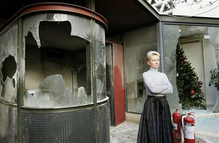 Catherine Suard, head of the French Institute, stands in front of broken windows following an attack with stones and firebombs by protesters in Athens December 19, 2008. REUTERS/John Kolesidis