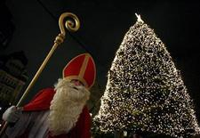 <p>A man dressed as Saint Nicholas stands beside an illuminated Christmas tree in the city center of Hamburg December 6, 2008. REUTERS/Christian Charisius</p>