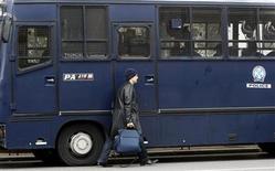 <p>Прохожий на фоне полицейского автобуса, стоящего возле здания парламента в Афинах 23 декабря 2008 года. Полицейский автобус подвергся обстрелу в Афинах во вторник утром на фоне третьей недели антиправительственных выступлений в Греции. REUTERS/Yiorgos Karahalis</p>