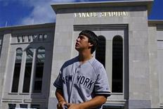 <p>A fan looks up at Yankee Stadium with the new stadium in the background in the Bronx borough of New York September 20, 2008. REUTERS/Eric Thayer</p>