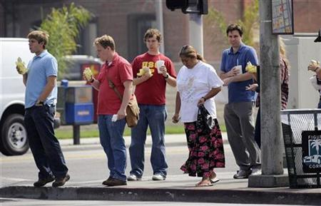 Customers hold fast food purchased at nearby restaurants in South Los Angeles, August 28, 2008. REUTERS/Phil McCarten