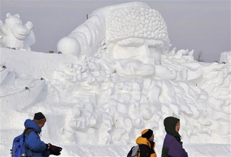 People visit a giant Santa Claus ice sculpture for the upcoming 25th Harbin International Ice and Snow Festival at a park in Harbin, Heilongjiang Province December 24, 2008. China's freezing northern city of Harbin is building what organisers say is the world's largest Santa Claus ice sculpture. REUTERS/Sheng Li