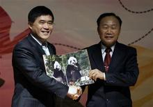 <p>Zhao Xue-min (der), presidente de la Asociación de Protección de la Vida Silvestre de China, presenta un retrato de los pandas Tuan Tuan y Yuan Yuan al alcalde de Taipei City, Hau Lung-bin, en Muzha, 24 dic 2008. Dos diputados taiwaneses bailaron el miércoles en el Parlamento vestidos con trajes de panda gigante para burlarse de la muy publicitada llegada de dos osos como regalo de buena voluntad de China, algo que consideran una interferencia no bienvenida del continente. REUTERS/Pichi Chuang (TAIWAN)</p>
