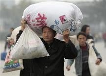 <p>A migrant worker carries his belongings at a railway station in Nanjing, Jiangsu province, in this November 6, 2008 file photo. REUTERS/Sean Yong/Files</p>