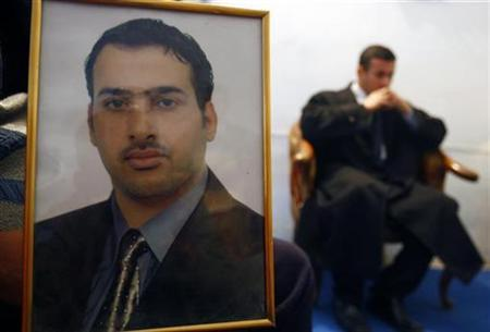 The brother of Muntazer al-Zaidi, a TV reporter from al-Baghdadiya who threw his shoes at U.S. President George W. Bush, displays his picture during an interview with Reuters in his apartment in Baghdad in this December 15, 2008 file photo. REUTERS/Atef Hassan