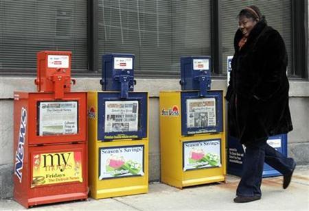 A woman walks past Detroit News and Detroit Free Press paper boxes in Detroit, Michigan December 16, 2008. REUTERS/Rebecca Cook