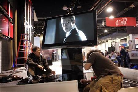 Workers at an LG booth set up a display featuring the 50PG60 television, a 50-inch 1080p plasma TV with a single layer design, as they prepare for the Consumer Electronics Show (CES) in Las Vegas, Nevada January 6, 2008. REUTERS/Steve Marcus