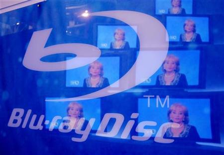 Television images are reflected on a sign for Blu-ray Discs at the 2007 International Consumer Electronics Show in Las Vegas, Nevada January 9, 2007. REUTERS/Rick Wilking
