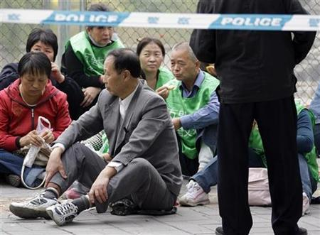 Protesters sit behind a police line outside a government office in central Beijing in this October 20, 2008 photo. REUTERS/David Gray