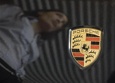 A sales woman is reflected on a Porsche car in a showroom in Almaty November 19, 2008. REUTERS/Shamil Zhumatov