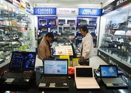 A man shops for computers and LCD monitors inside an electronics shop in Taipei in this November 20, 2008 file photo. The age of the desktop PC appears to be over as its more portable cousin, the laptop, surges ahead with consumers clamouring for light-weight computers in funky designs for use at home, in cafes and on the train to work. REUTERS/Nicky Loh/Files