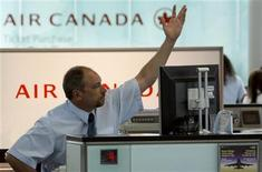 <p>An Air Canada employee gestures for the next passenger at the check-in counter at Pearson International Airport in Toronto in this June 17, 2008 file photo. REUTERS/ Mike Cassese</p>