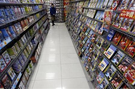 A woman walks inside a DVD rental shop in Taipei February 18, 2008. An impending end to a format war over next-generation DVDs boosted shares in both victorious Sony, in the Blu-ray corner, and Toshiba, in the losing HD DVD camp, on Monday as consumers cheered an end to confusion over which discs will carry high-definition movies. REUTERS/Nicky Loh
