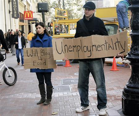 Tania Khadder (L), 29, and John Henion, 32, both unemployed online journalists, hold signs announcing a new blog called ''unemploymentality.com'' along Market Street in San Francisco, California in this December 9, 2008 file photo. REUTERS/Robert Galbraith/Files
