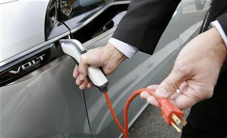 Larry Burns, General Motors vice president of Research and Development and Strategic Planning, demonstrates how to plug in a Chevy Volt on Capitol Hill in Washington in this December 4, 2008 file photo. REUTERS/Kevin Lamarque