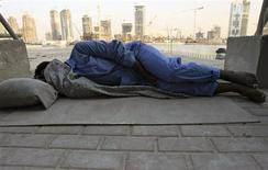 <p>A foreign worker sleeps on the sidewalk near a construction site in Dubai, United Arab Emirates, in this November 13, 2006 file photo. REUTERS/Ahmed Jadallah/Files</p>
